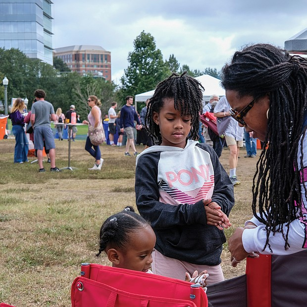 Faith Walker helps her 2-year-old niece Legacy and daughter Phoenix, 6, disinfect their hands at the Richmond Folk Festival on Brown's Island last weekend.  Thousands of people took part in the three-day cultural extravaganza that asked people to wear masks, use hand sanitizer, and maintain social distance to help curb the spread of COVID-19.  At the weekend, festival visitors were provided with free COVID-19 vaccines and hand disinfection stations on the premises.
